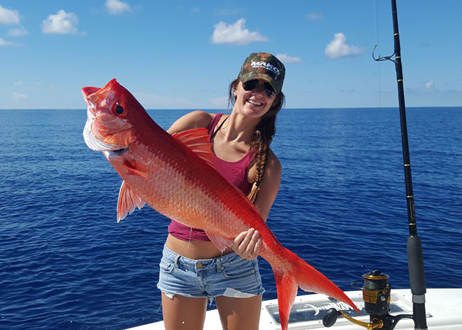 Valerie very excited lifting a colorful fish she caught during a fishing charter tour.